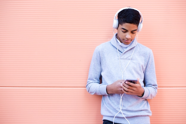 Black young man listens to music on his mobile phone while standing on the street.  african american teenager in headphones using a smartphone.
