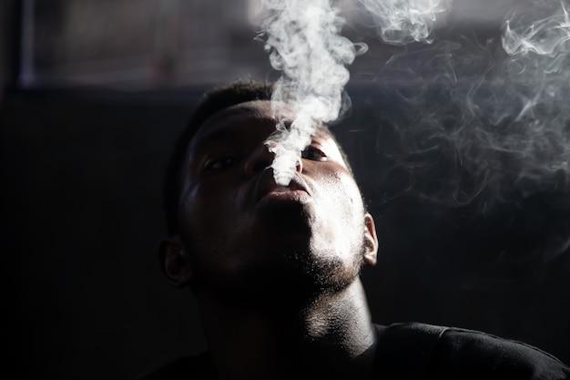 黒人の若い男の喫煙と煙を爆破