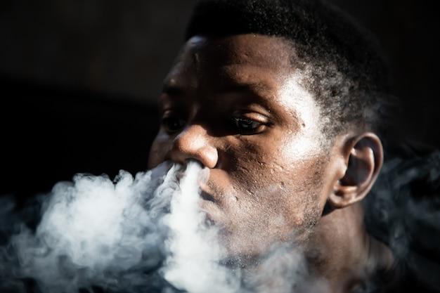 暗い部屋に座っている彼の鼻から喫煙黒人の若い男