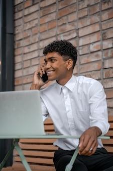 흑인 청년은 갈색 벽돌 벽을 배경으로 전화 통화를 합니다. 흰 셔츠를 입은 남자는 스마트폰과 노트북을 사용합니다. 사무실 밖에서 원격 작업. 세로 사진입니다.