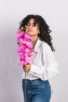 Black young woman holding pink flower
