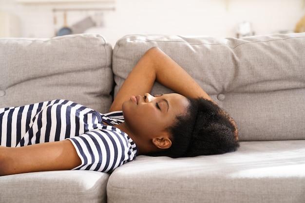 Черная молодая женщина носит раздетую футболку, отдыхая, спит на диване у себя дома с закрытыми глазами, делая перерыв