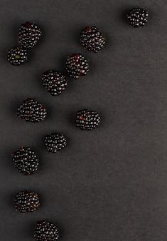 Blackberries on black background. copy space, vertical.