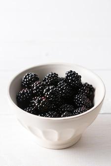 흰색 배경에 있는 그릇에 있는 블랙베리 클로즈업, 잘 익은 즙이 많은 베리