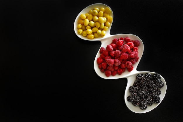 Blackberries and dogeberry in white plate on black background