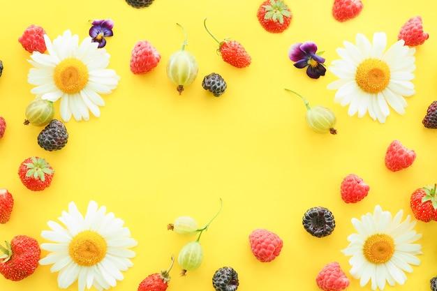 블랙베리, 구스베리, 라즈베리, 야생 딸기, 그리고 노란색 배경에 카모마일이 있는 딸기. 복사 공간입니다.