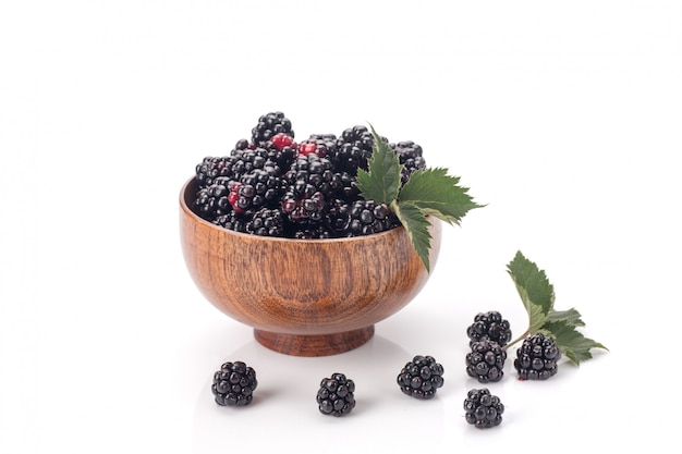 Blackberries in a wooden bow. ripe and tasty black berry isolated on white