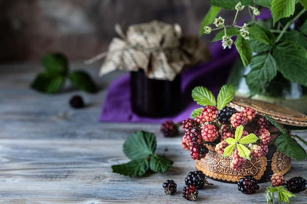Blackberry berry on a branch with leaves in a wooden carved box on a dark wooden background.