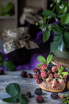 Blackberry berry on a branch with leaves in a wooden carved box on a dark wooden