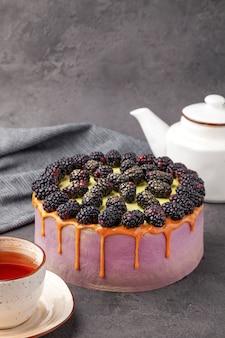 Ежевичный торт, чайник и чашка чая на серой поверхности