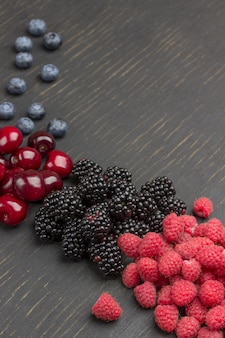 Blackberry, cherry, blueberry and raspberry on black surface. copy space. flat lay