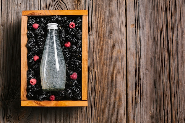 Blackberry juice bottle on wooden background