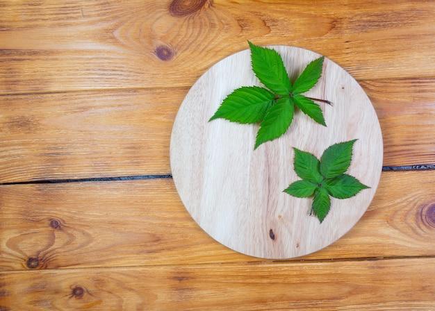 .ежевика листья на бамбуковой разделочной доске на деревянных фоне.