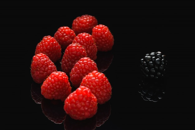 Blackberry and raspberry on a black table, differ from others.