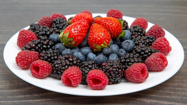 Blackberry, raspberry blueberry and strawberry on a white plate.