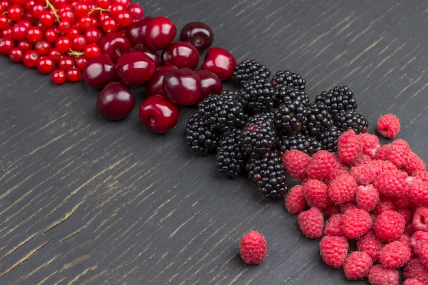 Blackberry, red currants, cherry, and raspberry on black surface. copy space. flat lay