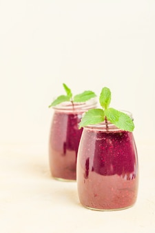 Blackberry smoothie - organic raw drink with fresh ripe forest berries on pastel yellow background.
