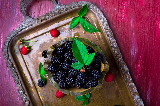 Blackberry with leaf in a basket on vintage metal tray,