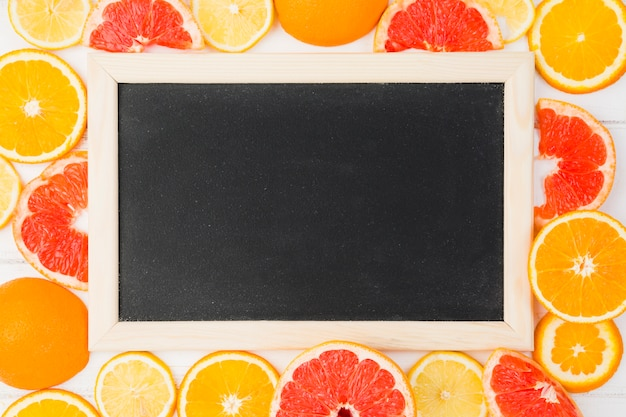 Blackboard among fresh grapefruits and oranges