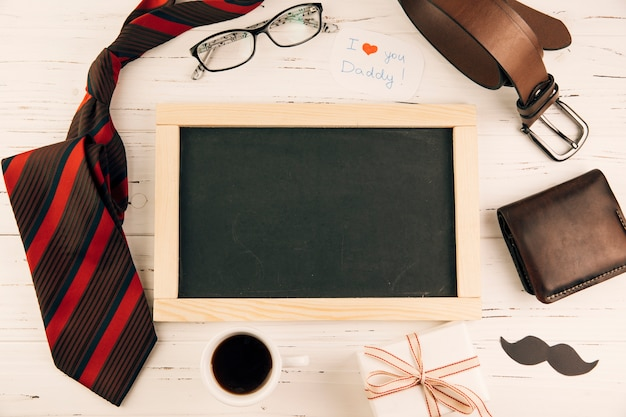 Blackboard among male accessories near gift and cup of drink