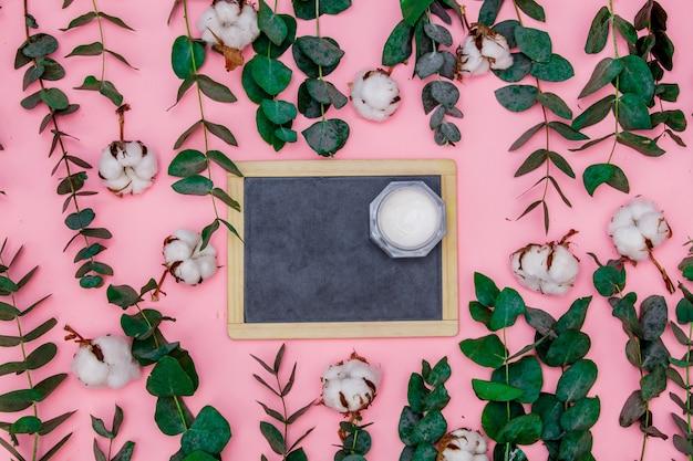 黒板とボディケアクリームは、ピンクのテーブルの上、ユーカリと綿の葉と枝の周りにあります