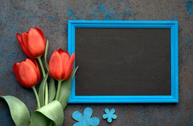 Доска и букет из красных тюльпанов и цветов ландыша на темном фоне, пространство