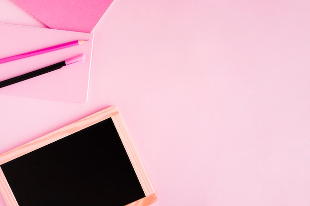 Доска и письменные принадлежности на цветной поверхности