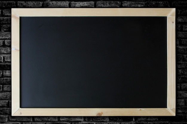 Blackboard background and wooden frame on brick wall background.