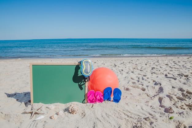 Blackboard and beach accessories on sand