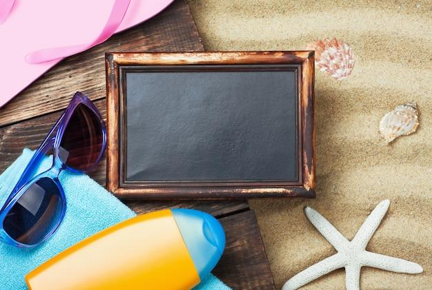 Blackboard and beach wear on the sand