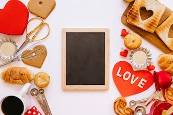 Blackboard between Valentine's day pastry
