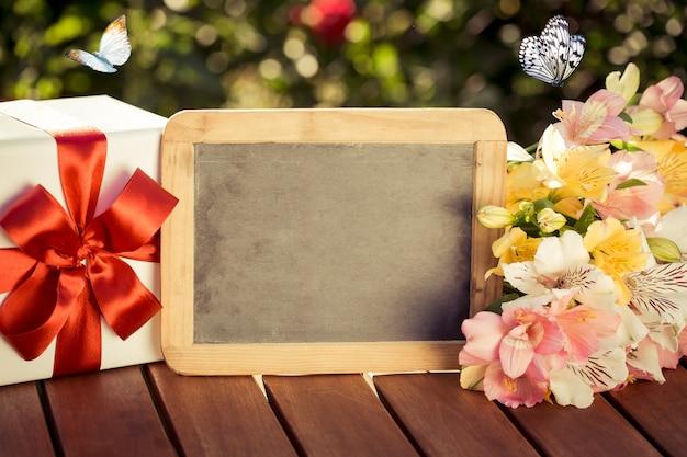 Пробел классн классного, подарочная коробка и цветы на фоне весны. женский день концепция.