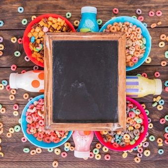 Blackboard on bright bowls of cereals and bottles
