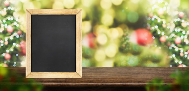 Blackboard on brown wood table top with blur christmas tree red decor ball