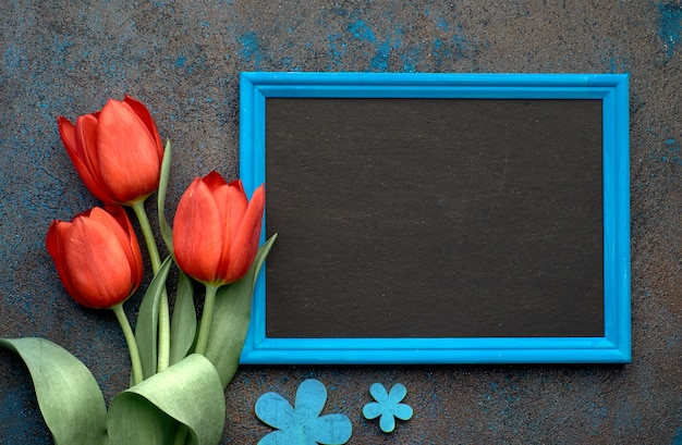 Blackboard and bunch of red tulips and lily of the valley flowers on dark background, space