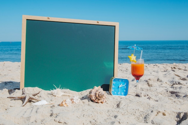 Blackboard and cocktail on beach