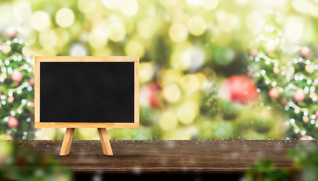 Blackboard on dark brown wood table with abstract blur christmas tree red decor ball and s