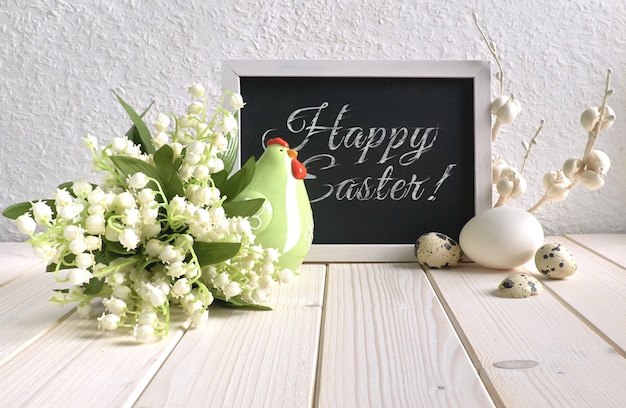Blackboard decorated with ceramic hen, eggs and and lily of the valley flowers, text