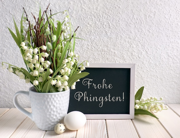 Blackboard decorated with lily of the valley flowers and eggs, text in german means