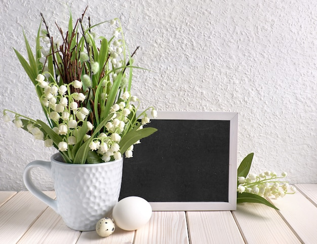 Blackboard decorated with lily of the valley flowers and eggs, text