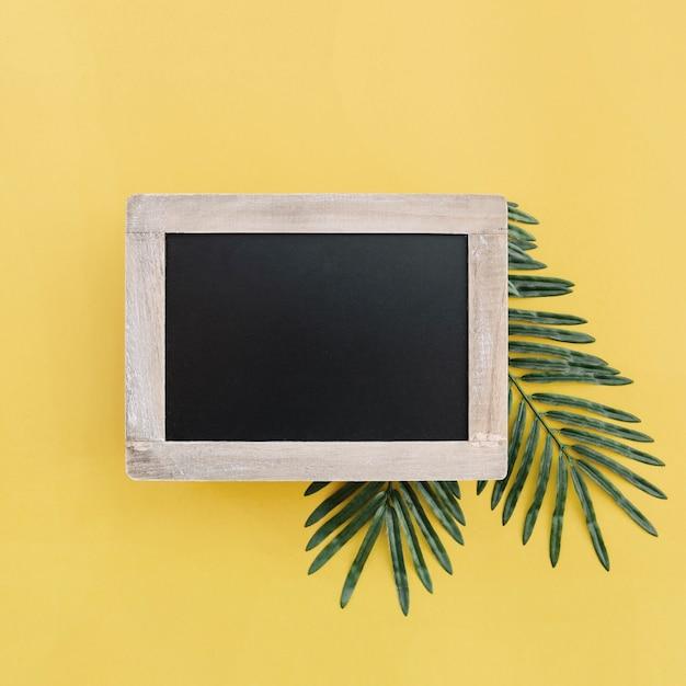 黄色の背景にヤシの葉でモックアップのための黒板