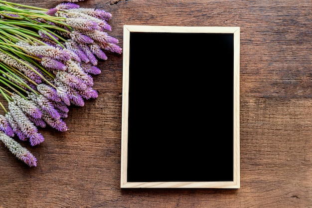 Blackboard frame and purple flower on wooden background