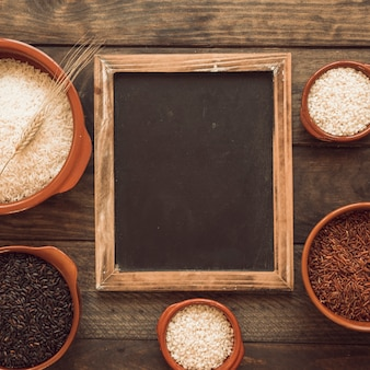 Blackboard frame with bowls of different rice on wooden table