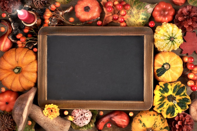 Blackboard framed with autumn decorations on wood, space