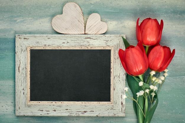 赤いチューリップと中立的な壁に木の心で囲まれた黒板