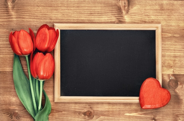 Blackboard framed with red tulips onl wooden background, space for your text