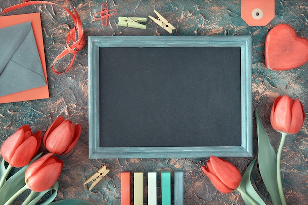 Blackboard framed with red tulips, wooden heart, color chalks and greeting envelopes on dark, text space