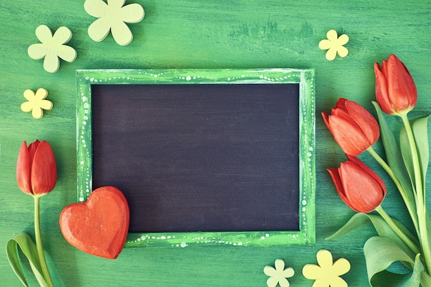 Blackboard framed with red tulips, wooden heart and flowers on green wood, space for your text