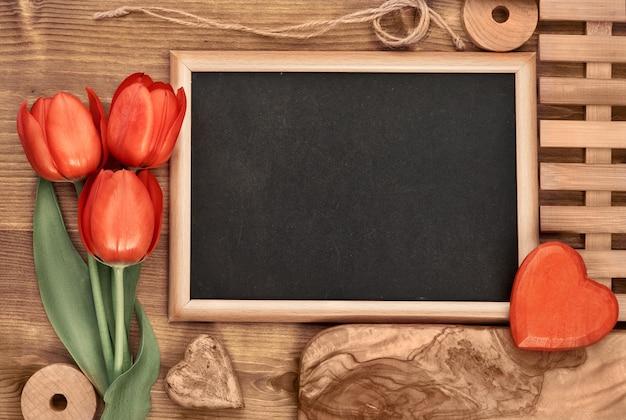 赤いチューリップで囲まれた黒板