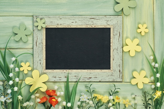 Blackboard framed with spring flowers on neutral background, copy-space